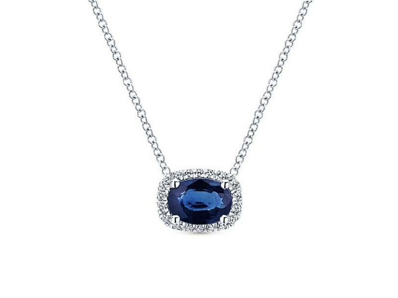 14K White Gold Pendant.  This Pendant Contains One Center Oval Blue Sapphire.  The carat weight of this sapphire is 1.00cts. This Sapphire Is Surrounded In A Halo Of Round Brilliant Cut Diamonds.  The Total Carat Weight Of These Diamonds Is 0.14Ctw  s823666